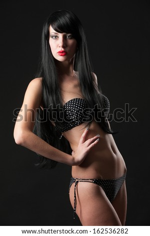 Photo of a young beautiful girl with long black hair on a dark background