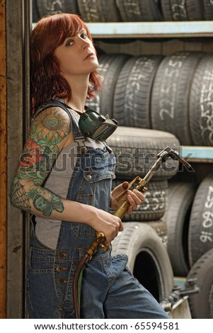 Photo of a young beautiful redhead mechanic wearing overalls and holding a welding torch.  Attached property release is for arm tattoos. - stock photo