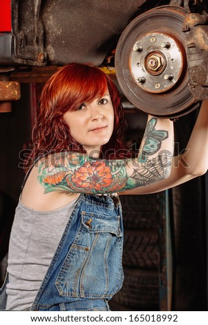 Photo of a young beautiful redhead mechanic wearing overalls and working on a car up on a hoist. Attached property release is for arm tattoos.  - stock photo