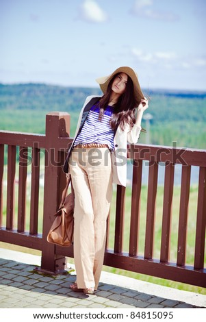 Photo of a young beautiful woman brunette fashion fabrics in today's casual elegant hat with a bag