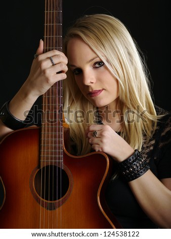 Photo of a young blond female holding an acoustic guitar.