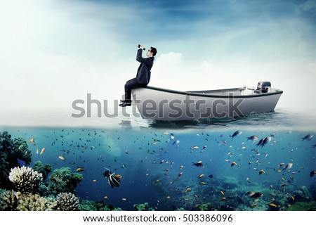 Photo of a young businessman sitting on a boat and looking through binoculars at the sea
