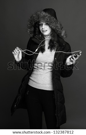 Photo of a young cheerful girl in warm jacket with headphones - stock photo