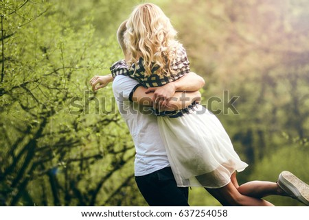 Photo of a young couple. A man in a white T-shirt turns a girl in a white flying out dress against the backdrop of an apple garden. Cute gentle photo ideal for advertising or banner