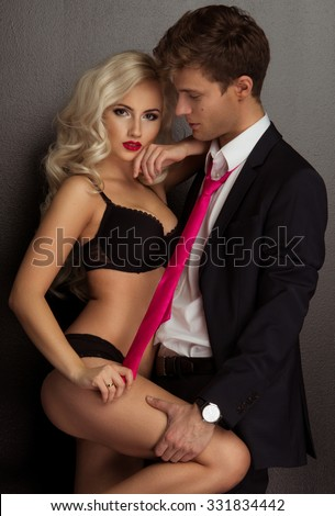 Photo of a young couple in sensual lingerie and suit