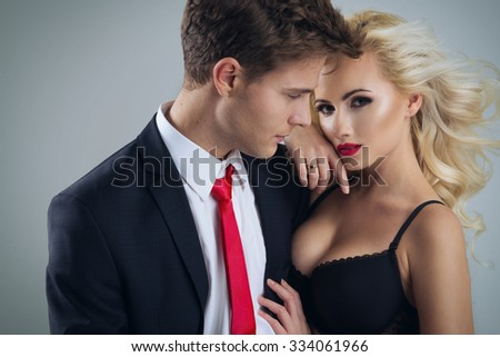 Photo of a young couple in sensual lingerie and suit  - stock photo