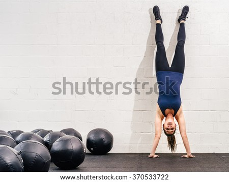 Photo of a young fit woman doing a handstand exercise at a crossfit gym. - stock photo
