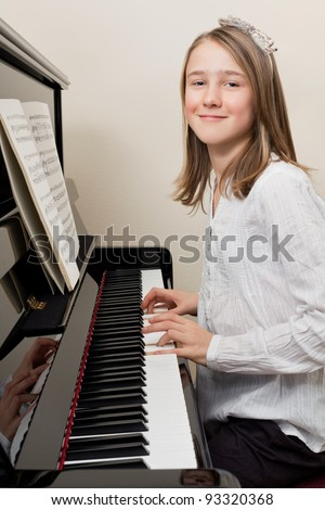 Photo of a young girl playing the piano at home. - stock photo