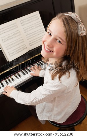 Photo of a young girl playing the piano at home. Sheet music has been altered to be unrecognizable. - stock photo