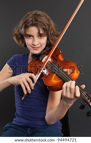 Photo of a young girl practicing the violin over a dark background. - stock photo