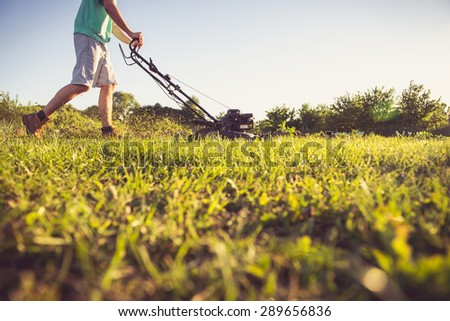 Photo of a young man mowing the grass during the beautiful evening. - stock photo