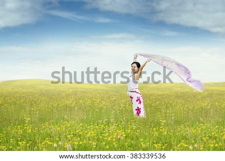 Photo of a young woman enjoy holiday while standing on the meadow with fabric
