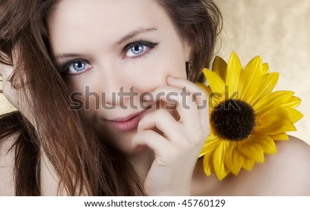 Photo of a young woman holding an artificial sunflower with a shiny bright smile over gold background. - stock photo