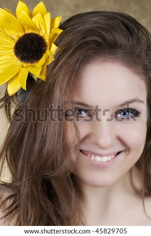 Photo of a young woman holding an artificial sunflower with a shiny bright smile over gold background.