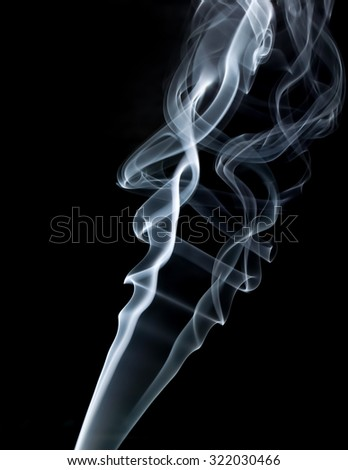 Photo of abstract smoke swirls on black background. Vertical shot.