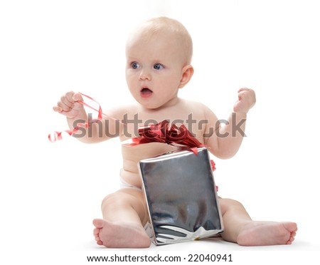 Photo of adorable toddler sitting with big giftbox by his side expressing joy - stock photo