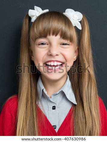 Photo of adorable young happy girl looking at camera at the black chalkboard in classroom. - stock photo