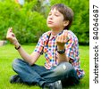 Photo of adorable young wise boy sitting on the grass at his backyard - stock photo