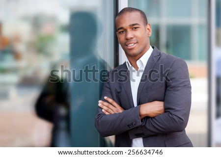 photo of african smiling businessman standing next to the glass wall - stock photo
