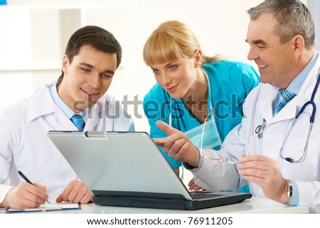 Photo of aged physician pointing at laptop display while explaining something to his colleagues - stock photo