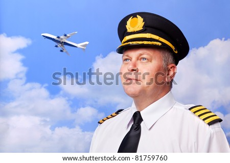 Photo of an airline pilot wearing the four bar Captains epaulettes, shot against a sky background with jumbo jet taking off in the distance. - stock photo