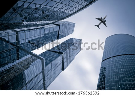 Photo of an airplane above the glass office buildings - stock photo