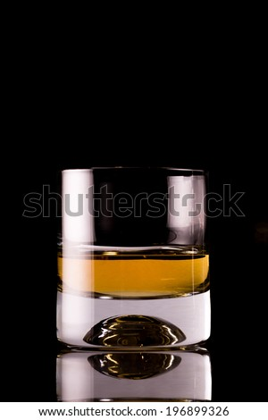 Photo of an alcohol glass, on a bar, dark background  - stock photo