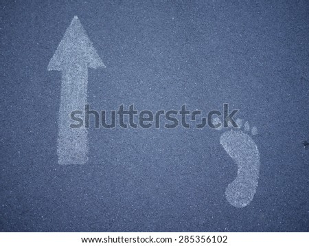 Photo of an asphalt road with white color signs. Arrow sign. Foot sign. Walking road concept. Footway symbol. Direction concept. - stock photo