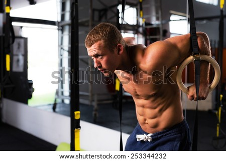 Photo of an athlete working out his muscles on rings - stock photo