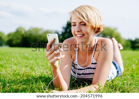 Photo of an attractive happy woman relaxing on the grass and listening to some music - stock photo