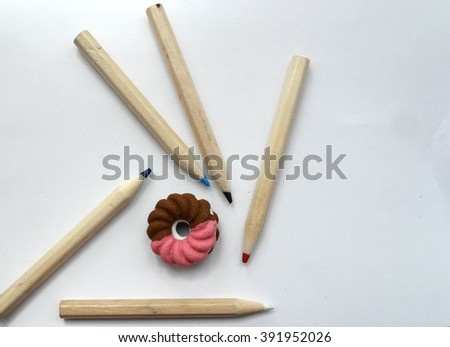 Photo of an eraser in the form of a brown and pink donut, and five small coloring pencils, on a white paper sheet. Rubber and pencils. Drawing tools. Sketching tools. Drawing as hobby. - stock photo