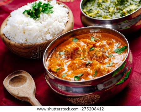 Photo of an Indian meal of Butter Chicken, rice and Saag Paneer. Focus across the Butter Chicken bowl. - stock photo