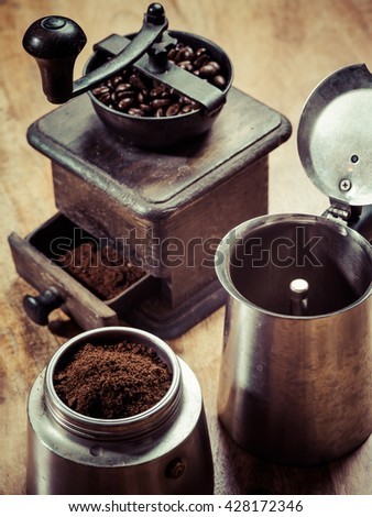 Photo of an Italian Moka Express stovetop coffee maker and a coffee grinder - stock photo