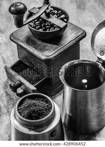 Photo of an Italian Moka Express stovetop coffee maker and a coffee grinder done in black and white. - stock photo