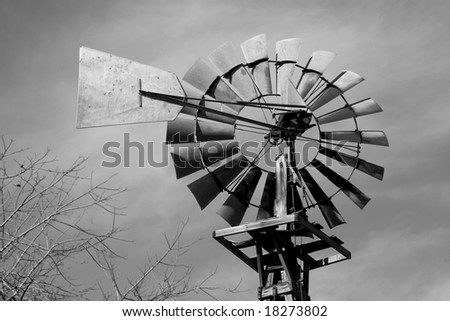 photo of an old farm windmill in black and white - stock photo