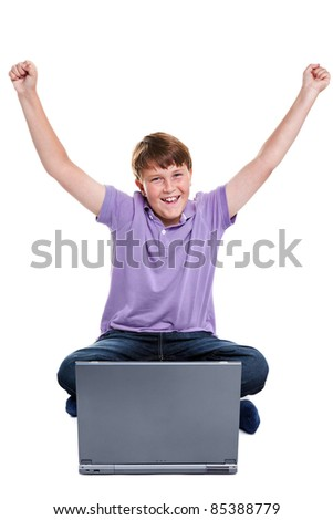 Photo of an 11 year old school boy sat with a laptop computer, his arms raised in the air, isolated on a white background. - stock photo