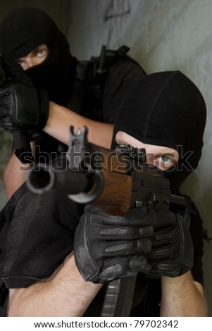 Photo of armed men in combat uniform playing terrorist or special forces team members - stock photo
