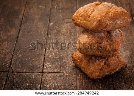 Photo of artisan ciabatta bread over over ancient wooden table - stock photo