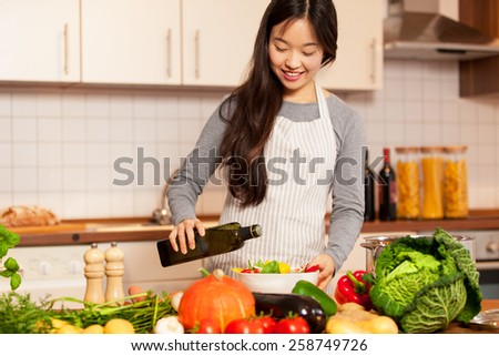 Photo of asian smiling woman pouring olive oil into the colorful salad