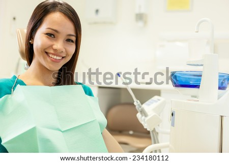 photo of asian young woman sitting at the dentist while smiling towards the camera - stock photo