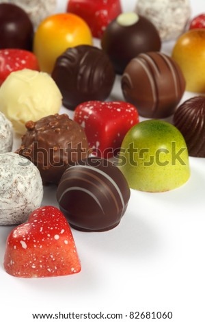 Photo of assorted truffles, pralines, and liqueur filled chocolates on white background. - stock photo