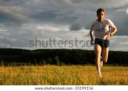 Photo of athlete in sportswear running outdoor - stock photo