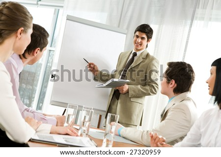 Photo of attentive business partners looking at successful entrepreneur pointing at whiteboard in office - stock photo
