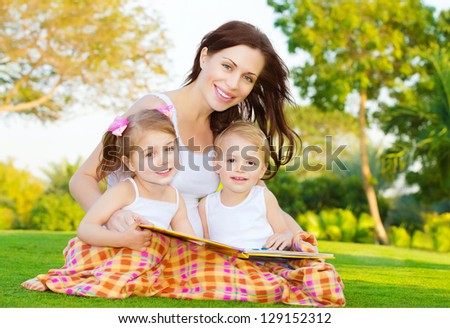 Photo of attractive brunette woman with two little smart children sitting down on green field in park in spring time and read book, mother with daughter and son enjoy fairytale, happy family concept - stock photo