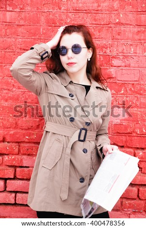 photo of Attractive young girl  reading a newspaper over a brick wall - stock photo