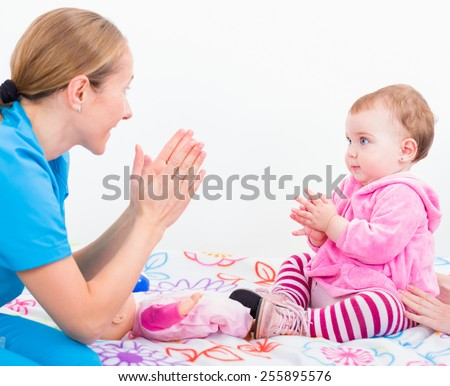 Photo of babysitter playing with an adorable baby - stock photo