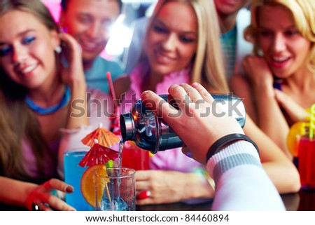 Photo of barman hand holding bottle and pouring water out of it - stock photo