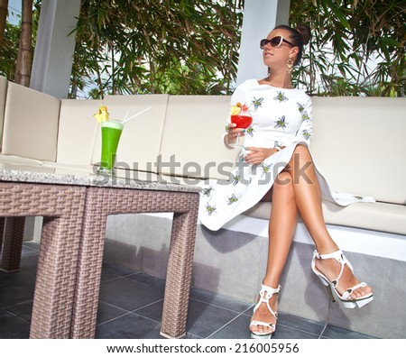 Photo of beautiful brunette woman with beautiful slim long legs sitting in a restaurant. Stylish rich gwomen in white dress. Glamorous lady at vacation. - stock photo