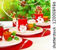Photo of beautiful Christmas table setting, New Year banquet, adorned evergreen tree, warm yellow sun light in dinning room, luxury porcelain dishware with red festive cup for tea, holiday decoration - stock photo
