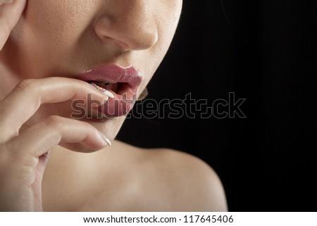 Photo of beautiful female lips and fingers - stock photo